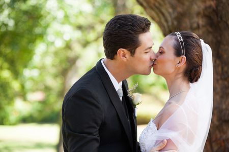 Side view of a romantic newlywed couple kissing in the park photo