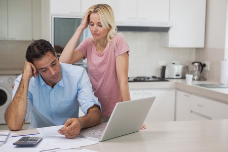 Unhappy couple with bills and laptop in the kitchen at home photo