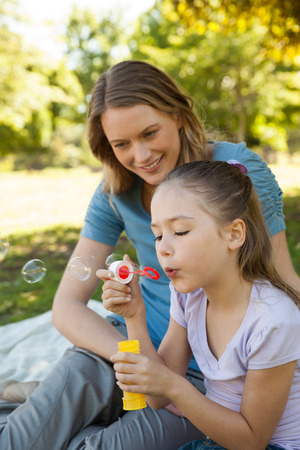 Side view of a mother with her daughter blowing soap bubbles at the park photo