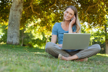 Portrait of a relaxed young woman using laptop and mobile phone at the park photo