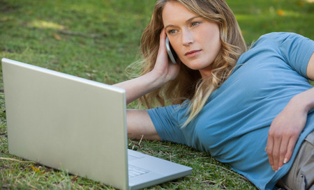 Relaxed young woman using laptop and mobile phone at the park photo
