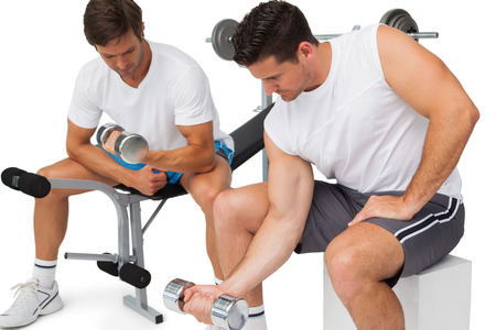 Two fit young men exercising with dumbbells over white background photo