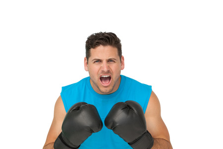 Close-up portrait of a determined male boxer screaming over white background photo