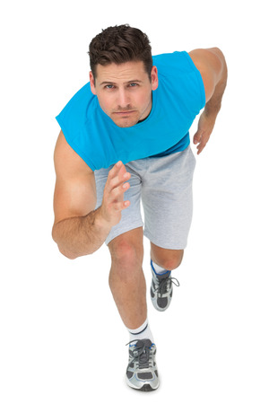 body concern: Portrait of a young sporty man running over white background