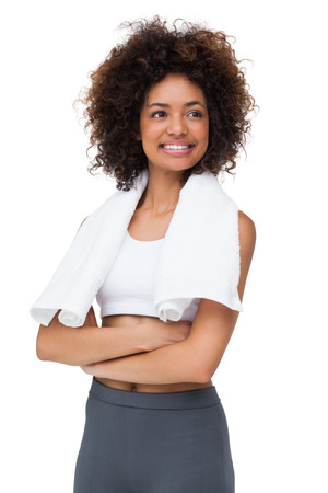 Smiling fit young woman with towel standing over white background photo
