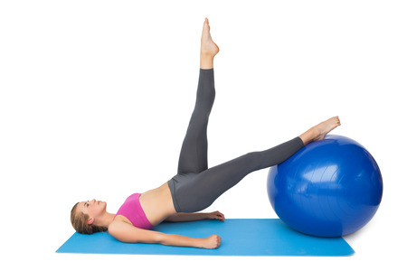Side view of a fit young woman exercising with fitness ball over white background photo