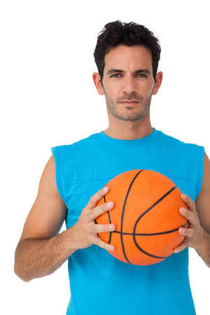 unsmiling: Portrait of a basketball player with ball isolated on white background Stock Photo