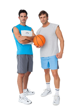 Full length of two fit young men with scales and basketball over white background photo