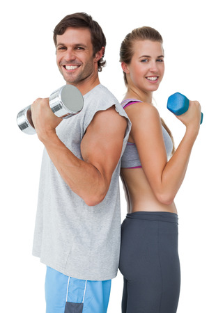 over white background: Portrait of a fit young couple exercising with dumbbell over white background