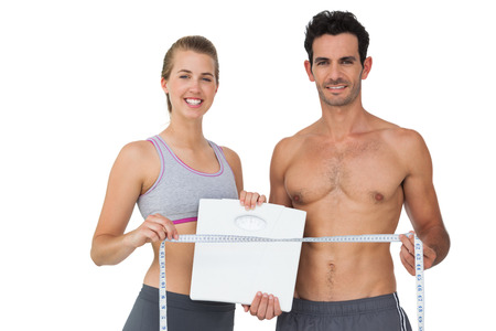 loss: Portrait of a sporty young couple holding scales and measuring tape over white background Stock Photo