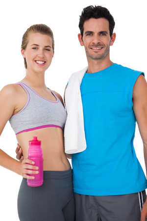 Portrait of a sporty young couple with water bottle and towel over white background photo
