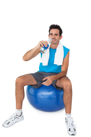 Portrait of a fit young man sitting on exercise ball while drinking water over white background photo