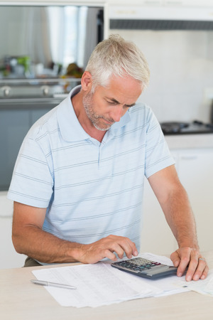 figuring: Focused man figuring out his finances at home in the kitchen Stock Photo