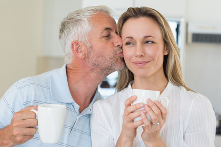 hot drink: Smiling man giving his partner a kiss on the cheek at home in the kitchen Stock Photo