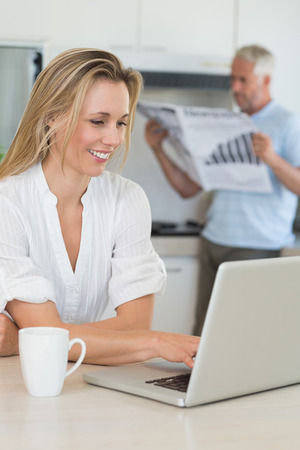 Smiling woman using laptop with partner standing with the paper at home in the kitchen photo