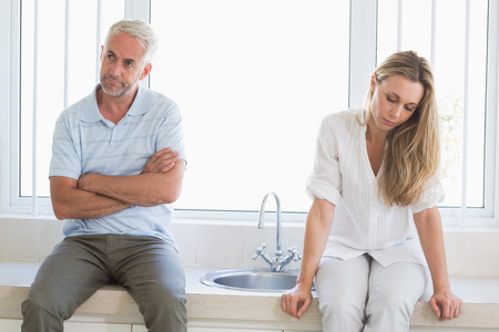 Upset couple not talking after an argument at home in the kitchen photo