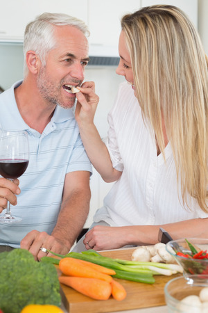 Affectionate couple preparing dinner together and drinking red wine at home in the kitchen photo
