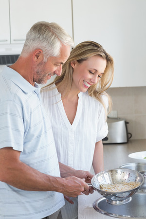 draining: Couple draining spaghetti in colander at home in the kitchen Stock Photo
