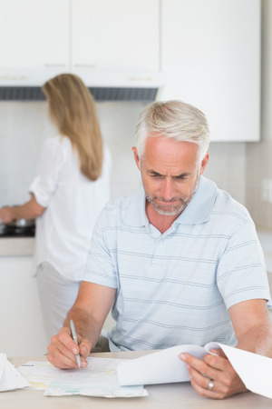 figuring: Worried man working out finances with partner standing behind at home in the kitchen