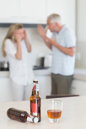 pareja discutiendo: Enojado pareja discutiendo después de beber alcohol en casa en la cocina Foto de archivo