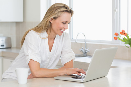 woman typing: Happy woman using laptop at counter at home in the kitchen Stock Photo
