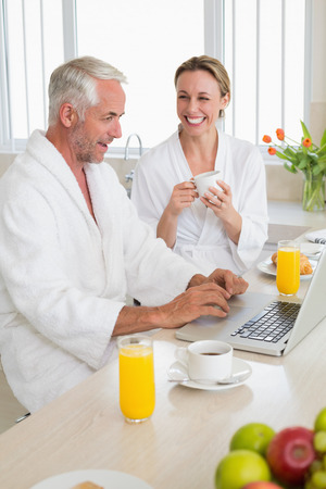 Smiling couple using laptop at breakfast in bathrobes at home in the kitchen photo