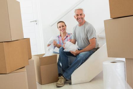 Coppia felice disimballaggio scatole di cartone in movimento nella loro nuova casa photo