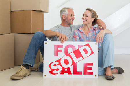 Happy couple sitting on floor with sold sign in their new home photo