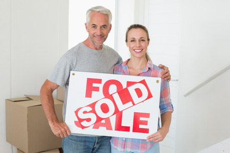 Happy couple standing and holding sold sign in their new home photo