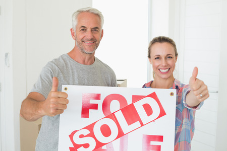 Happy couple standing and holding sold sign giving thumbs up in their new home photo