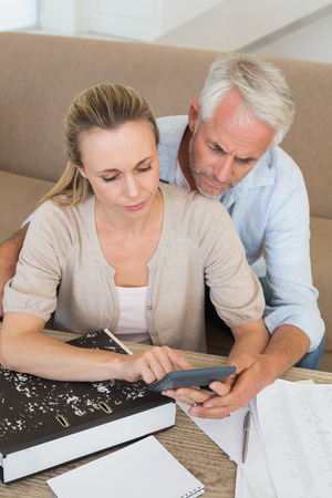 Serious couple calculating their bills at the couch at home in the living room Stock Photo - 27202388