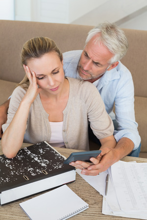 Serious couple calculating their bills at the couch at home in the living room Stock Photo - 27202389