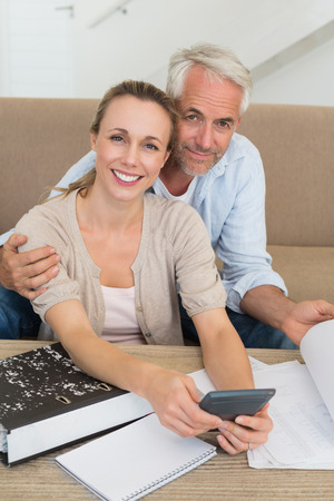 figuring: Smiling couple calculating their bills at the couch at home in the living room