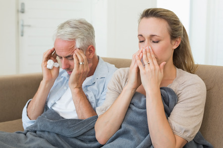 Sick couple sitting on the couch under a blanket at home in the living room photo