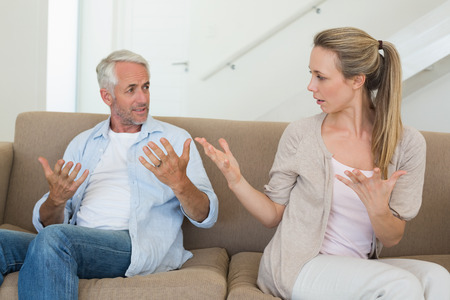 Angry couple sitting on couch arguing at home in the living room photo