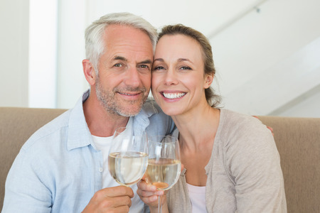 Happy couple sitting on couch toasting with white wine at home in the living room photo