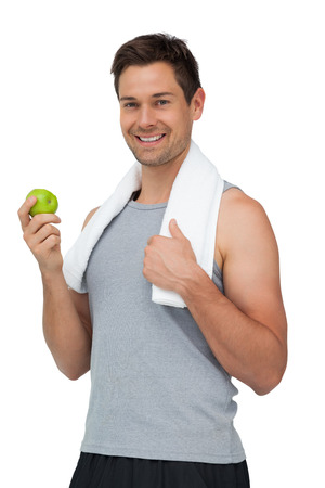 Portrait of a smiling fit young man with apple standing over white background photo