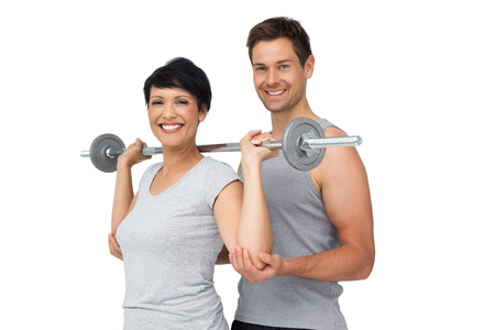 Personal male trainer helping young woman with weight lifting bar over white background