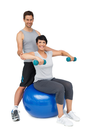 Portrait of a male trainer assisting woman with dumbbells over white background photo