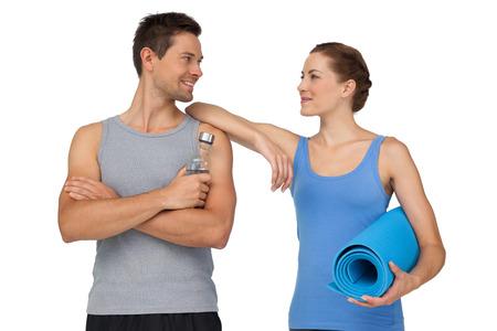 Retrato de una feliz pareja de jóvenes en forma con ejercicio estera y una botella de agua sobre fondo blanco