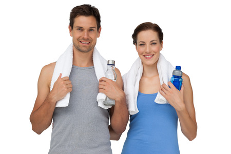 Portrait of a happy fit young couple with water bottles over white background photo