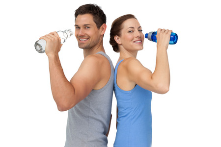 standing water: Portrait of a happy fit young couple with water bottles over white background