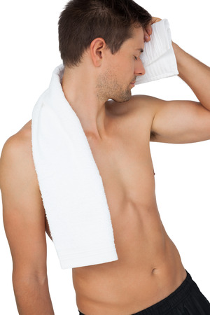Shirtless tired man with towel standing over white background photo