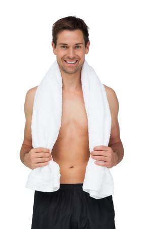 Portrait of a smiling shirtless man with towel standing over white background photo