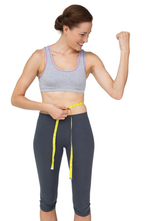 girth: Fit woman measuring waist while flexing muscles over white background Stock Photo