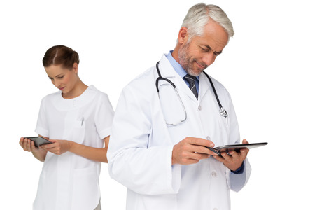 over white background: Male and female doctors using digital tablets over white background Stock Photo