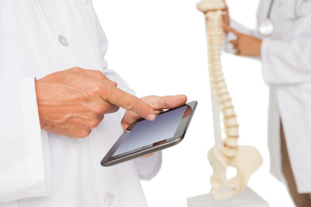 Close-up mid section of female doctor using digital table and colleague by skeleton model over white background photo