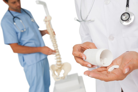 Close-up mid section of female doctor with pills and colleague by skeleton model over white background photo