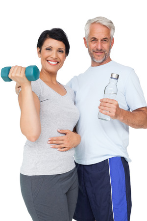 Portrait of a happy fit couple with dumbbell and water bottle white background photo