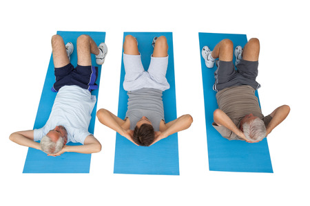 Full length of three men doing abdominal crunches over white background photo